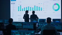 Project Leader, Chief Executive Discuss Data Shown on Big Display. Screens Show Infographics, Charts, Finance Analysis, Stock Market, Growth.Telecommunications Control Room with Working Professionals