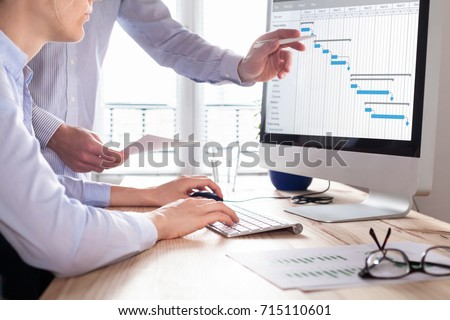 Project management team updating Gantt chart schedule or planning on computer, two business people in office