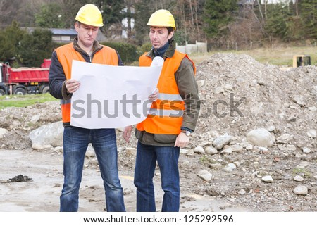 Project manager and architect are standing in a construction site looking in a construction plan