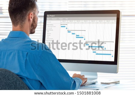 Project manager in office scheduling tasks and progression of milestones completion with Gantt chart planning on computer, professional time management software
