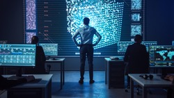 Project manager Stands Next to Big Screen with Neural Network. Team of Professional Computer Data Science Engineers Work on Desktops in a Dark System Control and Monitoring Telecommunications Office.
