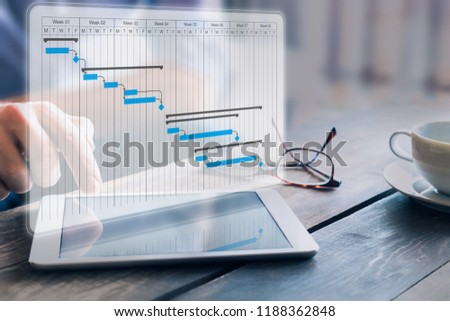 Project manager updating progress and deliverables milestones schedule on gantt chart planning with digital tablet computer, professional planner in office #1188362848