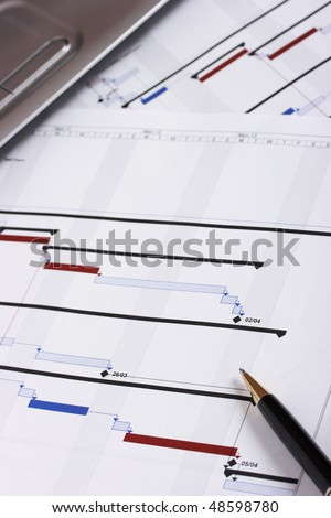 Project plan with pen in foreground and laptop in background