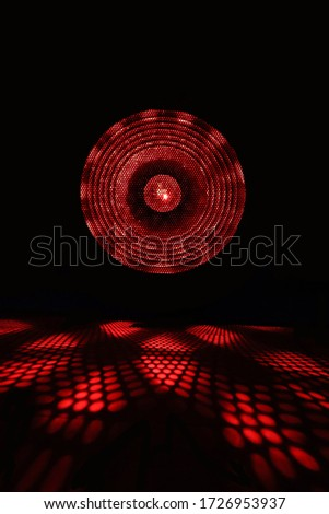 Projector of light rays. Red light show on black background. stock photo