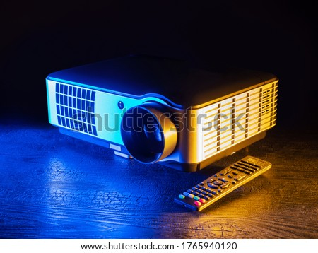Projector on a dark background. Remote control from projector. Concept - sale of equipment for presentations. Home cinema equipment. Conference room projector. Concept - slide show and presentation