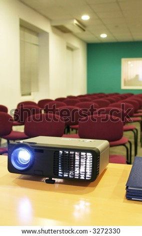 Projector on table with chairs behind in empty hall (vertical)