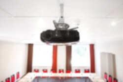 Projector on the ceiling. Interior of empty modern meetingroom. Conference room in a hotel for business training. Rows of chairs and desks. Blurred concept.
