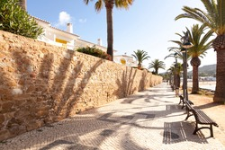 Promenade at Luz beach, Praia da Luz, with the typical portuguese sidewalk with palm trees and wooden benches facing the sea. Sunny morning with blue clear sky. Algarve, Lagos, Portugal.