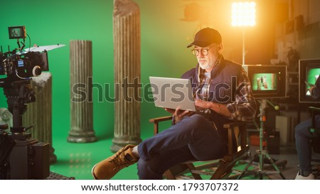 Prominent Successful Director Sitting in a Chair on a Break Using Laptop Computer. On the Studio Film Set with High-End Equipment Professional Crew Shooting High Budget Movie Сток-фото ©