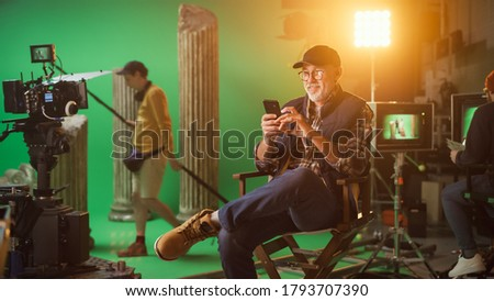Prominent Successful Director Sitting in a Chair on a Break Using Smartphone. On the Studio Film Set with High-End Equipment Professional Crew Shooting High Budget Movie. Сток-фото ©