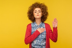 Promise to tell truth! Portrait of woman with curly hair raising hand to take oaths, promise to speak only truth, be sincere and honest, trustworthy evidence. studio shot isolated on yellow background