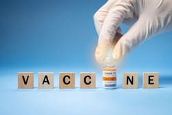 Promising Covid-19 Vaccine concept. Hand of a researcher take a 2019-nCov vaccine vial with wooden alphabet letters