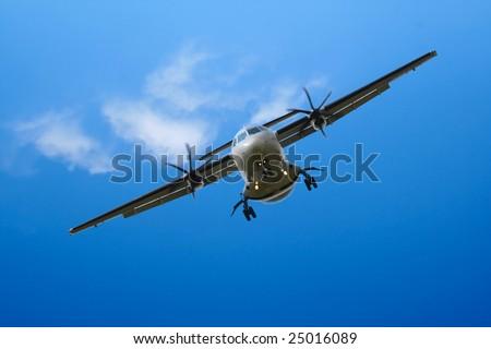 propeller airplane landing in cloudy blue sky