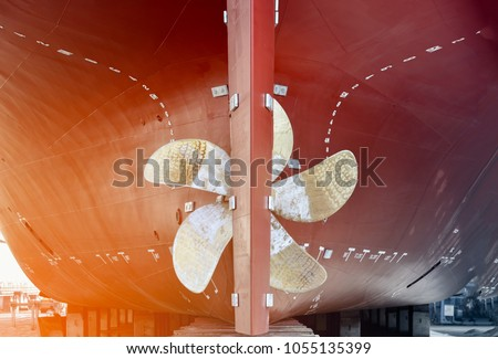 propeller closeup of container ship in floating dry dock of shipyard