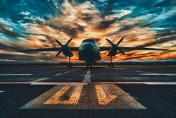 Propeller driven aircraft parked at sunset