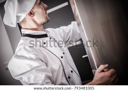 Proper Restaurant Food Storage. Caucasian Chef in His 30s Checking on the Fresh Products in the Commercial Restaurant Refrigerator.