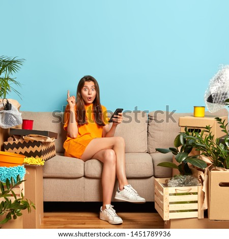 Property and rent concept. Surprised lady raises index finger, gets excellent idea for designing room, holds smartphone and surfes internet, moves in new apartment with luggage, sits on sofa