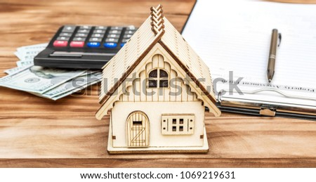 Property assessment form with money, calculator and model of house on the table. Property valuation concept.