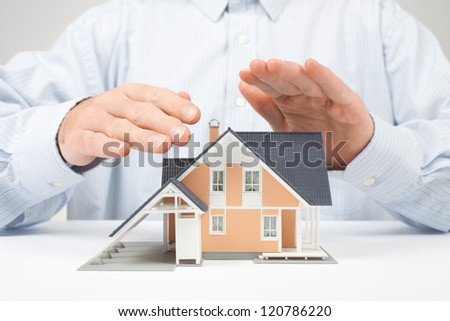 Property insurance concept - man protect model of the house.