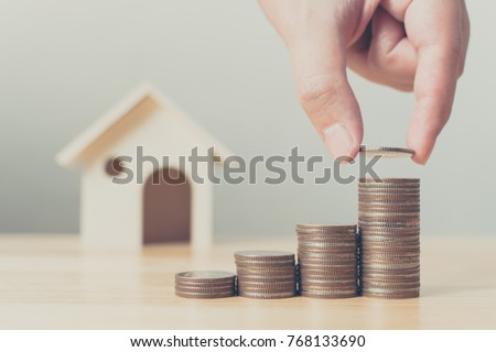 Property investment and house mortgage financial concept, Hand putting money coin stack with wooden house