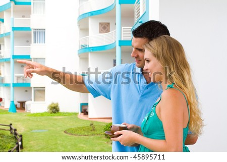 property investment - young couple drinking coffee on new home balcony