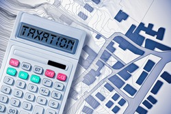 Property Tax on buildings concept image with an imaginary cadastral map and calculator with taxation text written on it.