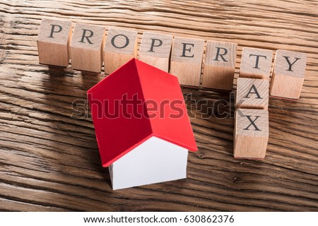 Property Tax Wooden Blocks With A Miniature House On Wooden Table