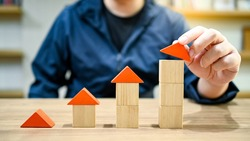 Property value concept. Real estate investment. Home loan or mortgage interest rate growth. Male hand placing house model piece to build the growing graph shape on wooden table.