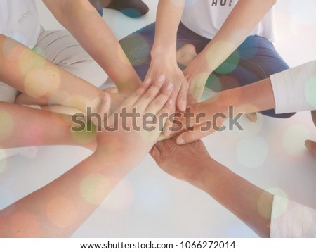 Prople of diferrent age with stack of hands showing unity and teamwork #1066272014