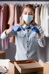 proprietor in medical mask, taking photo of box with clothes in showroom
