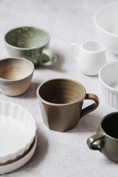 Props. Various of ceramics ware. Working process. On the grainy  textured white table. Tableware. Selective focus.