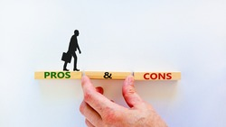 Pros and cons symbol. Wooden blocks with words 'Pros and cons'. Beautiful white background, businessman hand, businessman icon. Business, pros and cons concept, copy space.