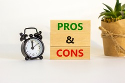 Pros and cons symbol. Wooden blocks with words 'Pros and cons'. Beautiful white background, black alarm clock, house plant. Business, pros and cons concept, copy space.