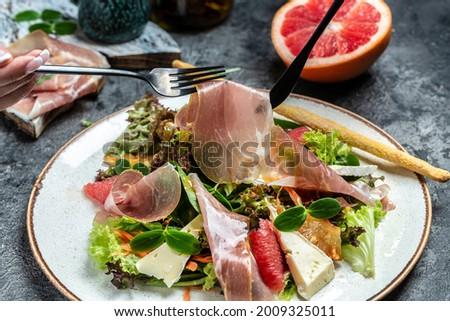 Prosciutto crudo ham salad with brie camembert cheese and grapefruit, salad mix. Restaurant menu, dieting, cookbook recipe. Foto stock ©
