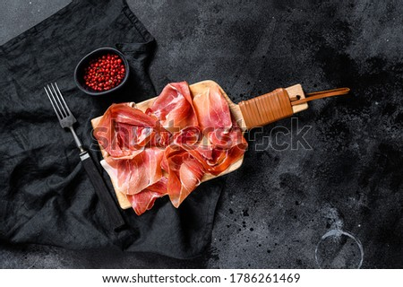 prosciutto crudo, italian salami, parma ham. Antipasto plate. Black background, top view, space for text Foto stock ©