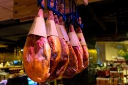Prosciutto di parma hams in the store. Pork legs or prosciutto. Spanish jamon in the market. Jamon Iberico pork black leg, traditional meat of Spain, serrano prosciutto on the background of gastronomy