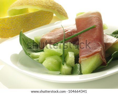 Prosciutto slices with melon pieces and herbs