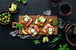 Prosciutto toasts served with wine and assorted olives, simple party appetizer idea, top down view