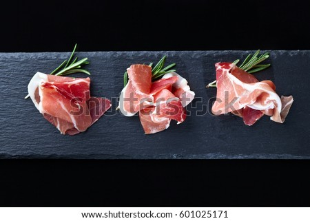 prosciutto with rosemary on a black background, top view