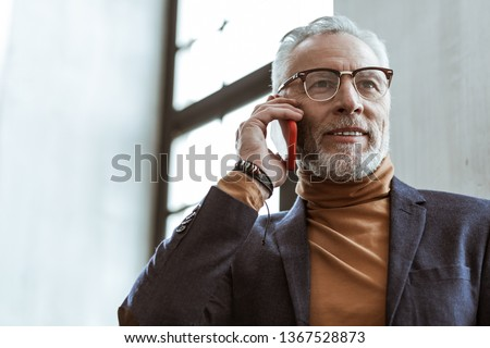 Prosperous businessman. Prosperous businessman calling his business partner standing near window in the office