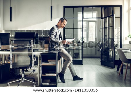 Prosperous businessman. Stylish prosperous businessman sitting in the office and reading documents