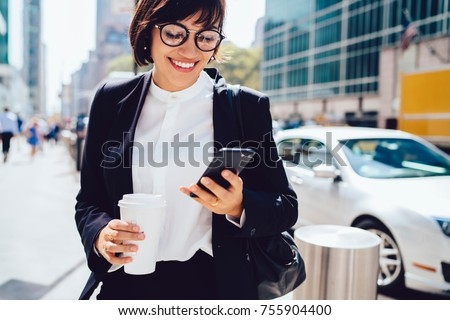 Prosperous Female entrepreneur in formal wear smiling while reading message on cellular walking on street, cheerful businesswoman satisfied with successful news sending feedback on phone strolling