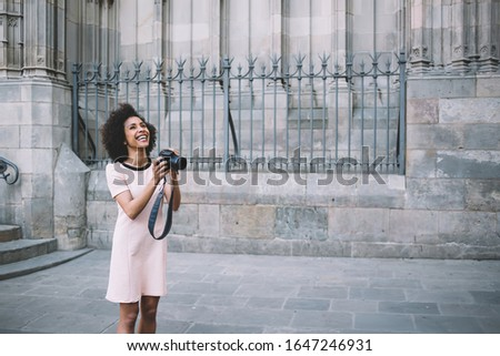 Photo of Prosperous female photographer with professional camera choosing views for taking pictures with ancient buildings, joyful woman with toothy smile enjoying free time for practicing with skills
