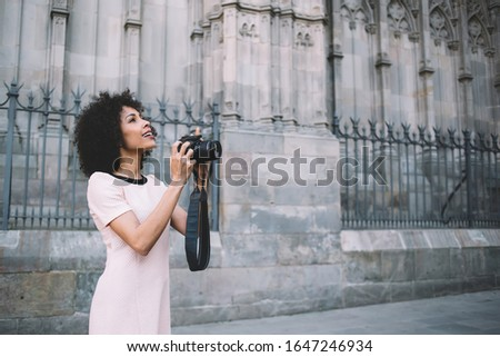 Photo of Prosperous female photographer with professional camera choosing views for taking pictures with ancient buildings, dark skinned woman with cute smile enjoying free time for practicing with skills