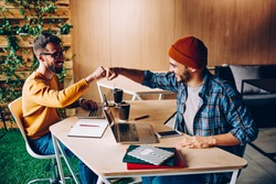 Prosperous male it developers clinking fists in sign of agrement cooperating on common startup project, young hipster guys greeting while meeting in coworking space for working creative together