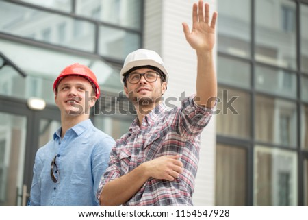 prosperous master builders waving hands. greeting concept. low angle view #1154547928