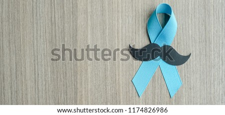 Prostate Cancer Awareness, light Blue Ribbon with mustache on wooden background for supporting people living and illness. Men Healthcare and World cancer day concept - Shutterstock ID 1174826986