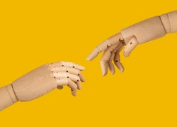 prosthetic hands touching each other. micheangelo the creation of adam hands and fingers isolated with yellow background. AI KI robot hands gesturing.