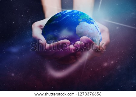 Protect our world in human hands and nebula dust. Mixed media. Elements of this image furnished by NASA.