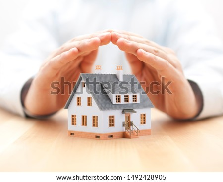 Protect your house concept. Small toy house covered by hands